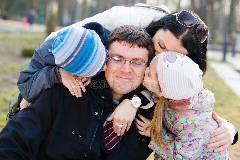 Lycklig familj av 4 som firar: Föräldrar med två barn som har gyckel som kramar, & kyssande fader, som är det lyckliga leendet, c royaltyfri bild
