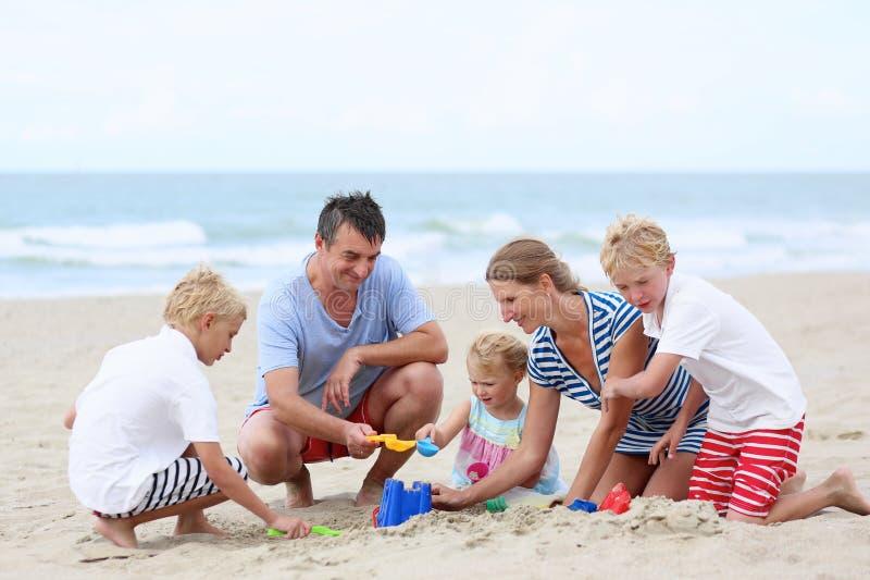 Lycklig familj av 5 som har gyckel på stranden royaltyfria foton