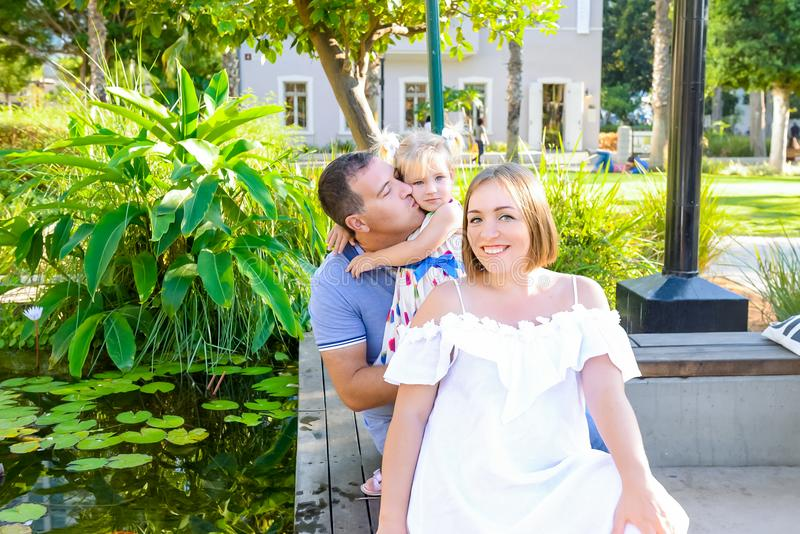 Lycklig familj av tre - gravid fru, fader och dotter som har det roliga near dammet med näckrors i parkera Familjrekreation, fotografering för bildbyråer