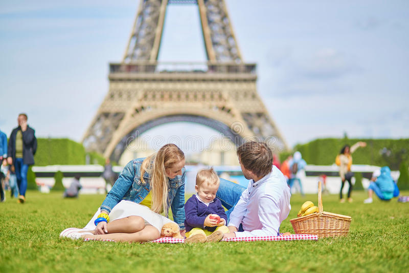 Lycklig familj av tre i Paris nära Eiffeltorn arkivbilder