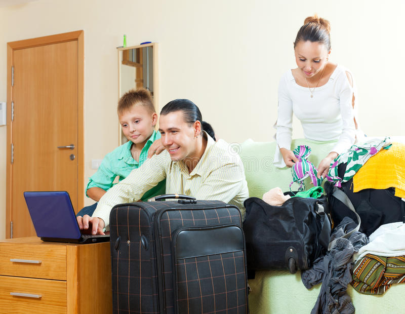 Lycklig familj av tre med den tonårs- pojken som väljer semesterorten på th arkivfoto
