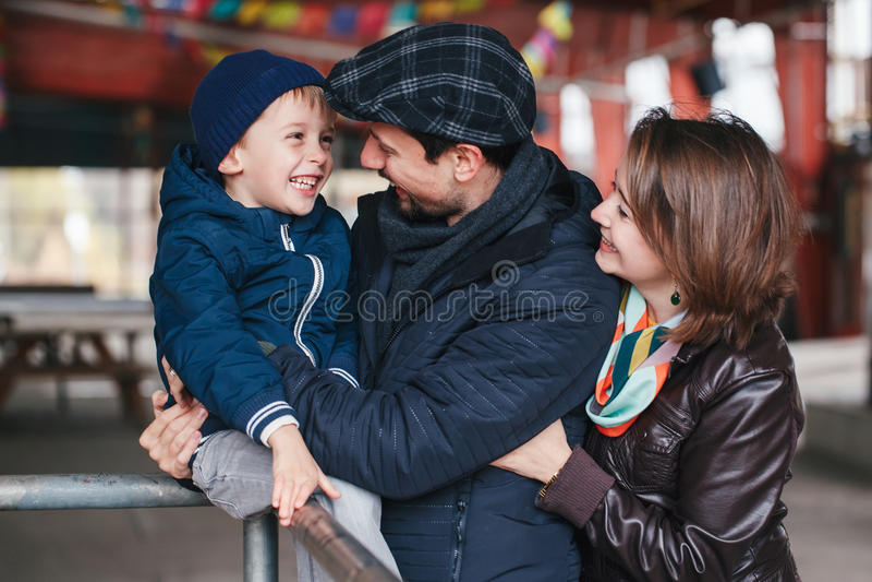 lycklig familj av tre moder, fader och son som ler skratta samtal till varandra, arkivfoton