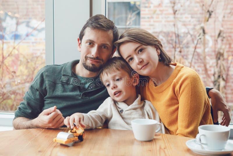 Lycklig familj av tre moder, fader och son som sitter i restaurang royaltyfri bild