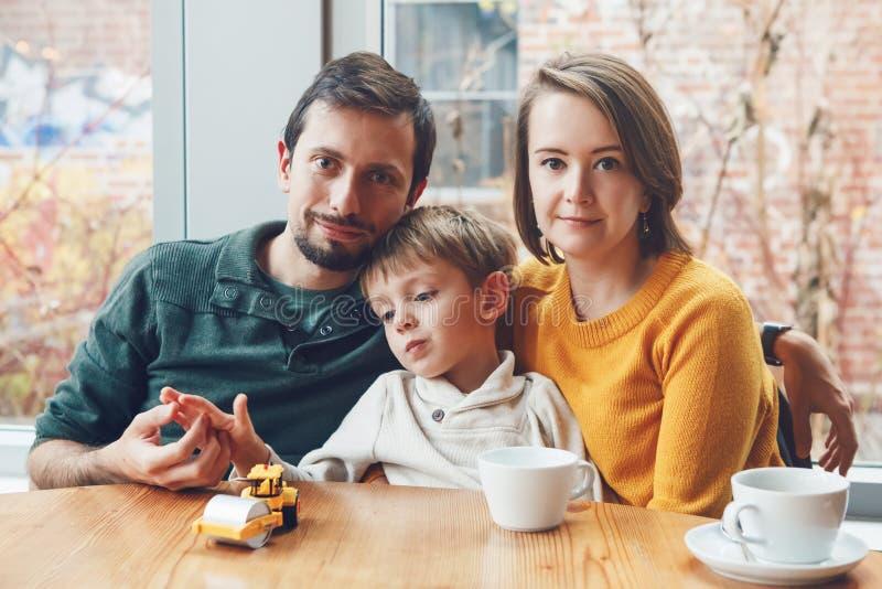 Lycklig familj av tre moder, fader och son som sitter i restaurang fotografering för bildbyråer
