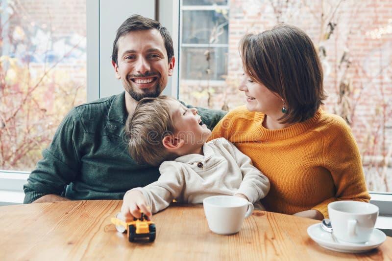 Lycklig familj av tre moder, fader och son som sitter i restaurang royaltyfria bilder