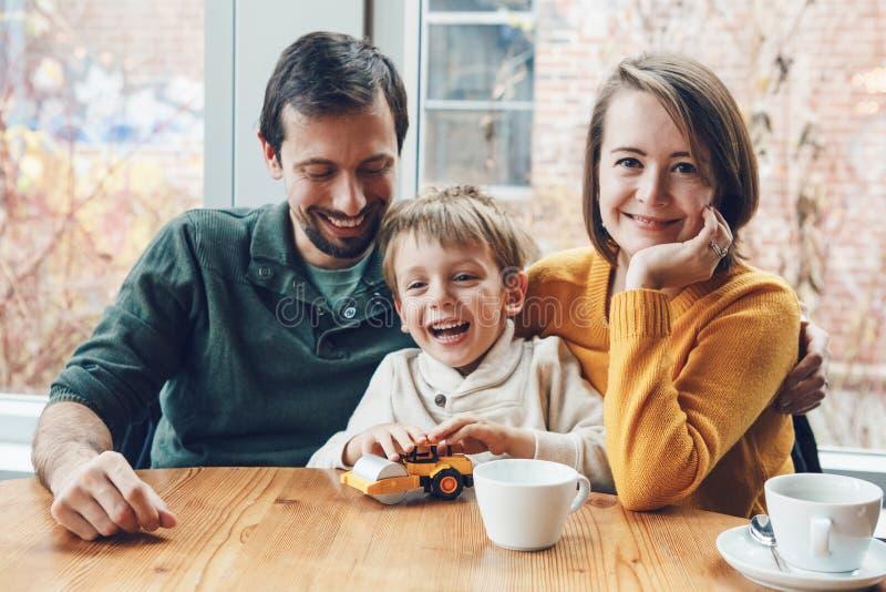Lycklig familj av tre moder, fader och son som sitter i restaurang royaltyfri fotografi