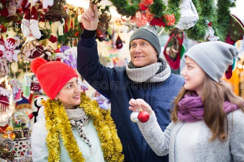 Lycklig familj av tre på julmarknaden arkivbild