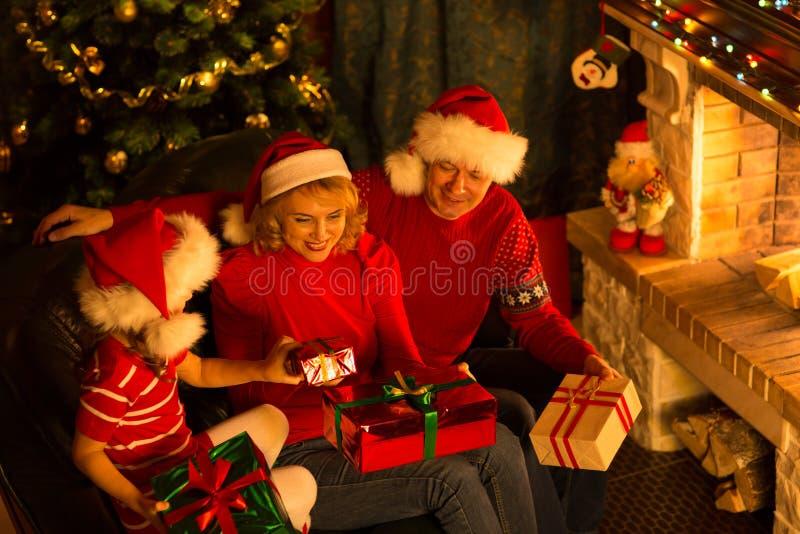Lycklig familj av tre personer i röda hattar med royaltyfri foto