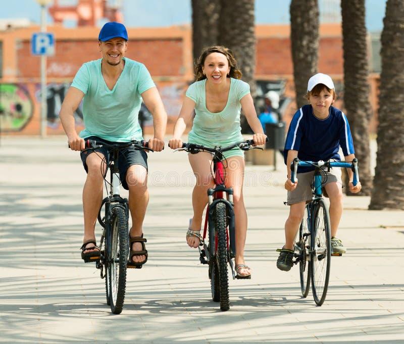 Lycklig familj av tre som cyklar över stad fotografering för bildbyråer