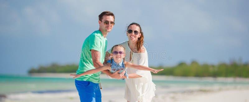 Lycklig familj av tre som har gyckel tillsammans på stranden royaltyfri fotografi