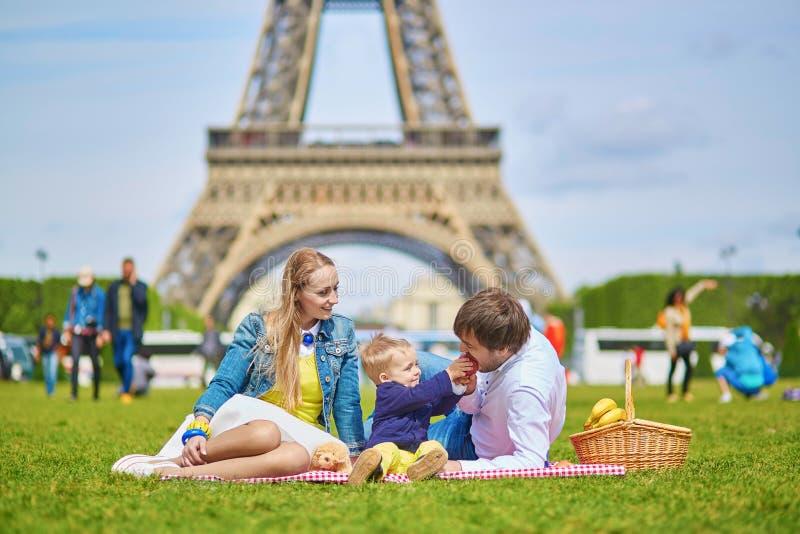 Lycklig familj av tre som har picknicken i Paris royaltyfri foto