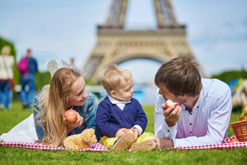Lycklig familj av tre som har picknicken i Paris royaltyfri bild