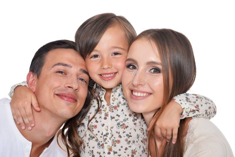 Lycklig familj av tre som ler och kramar p? vit bakgrund arkivbild