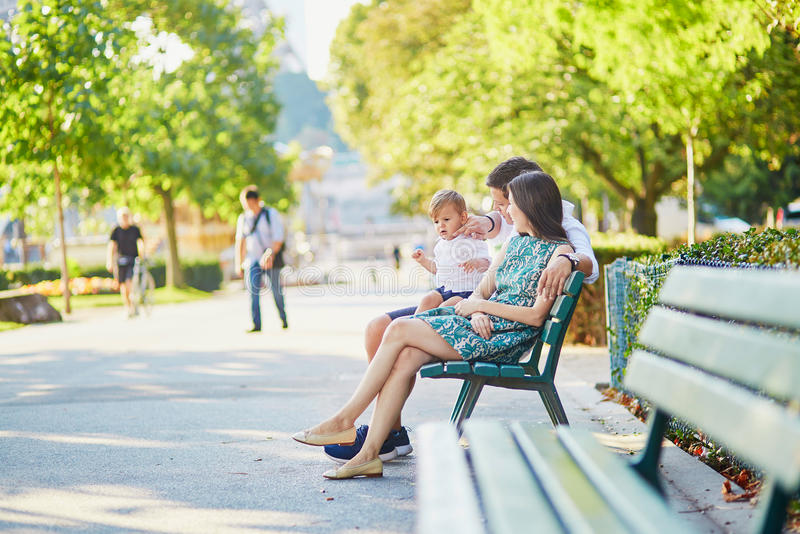 Lycklig familj av tre som sitter på bänken nära Eiffeltorn royaltyfri fotografi