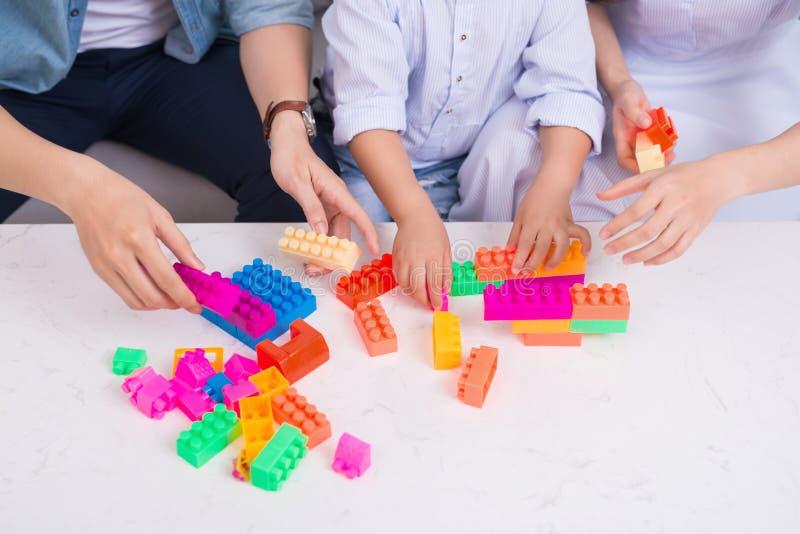 lycklig familj Barnet fostrar och avlar att spela med deras son, medan spendera tid tillsammans hemma arkivfoton