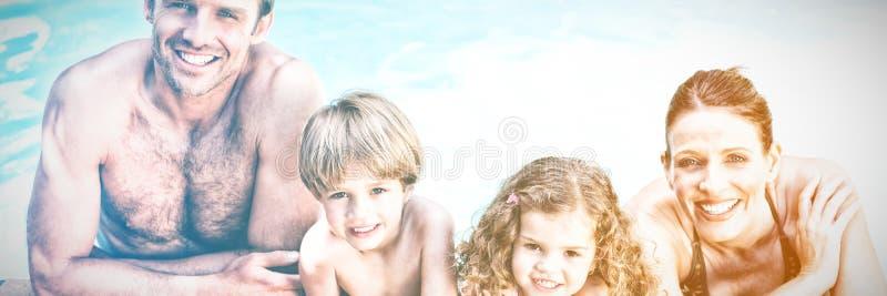 Lycklig familj bredvid simbassängen arkivfoton