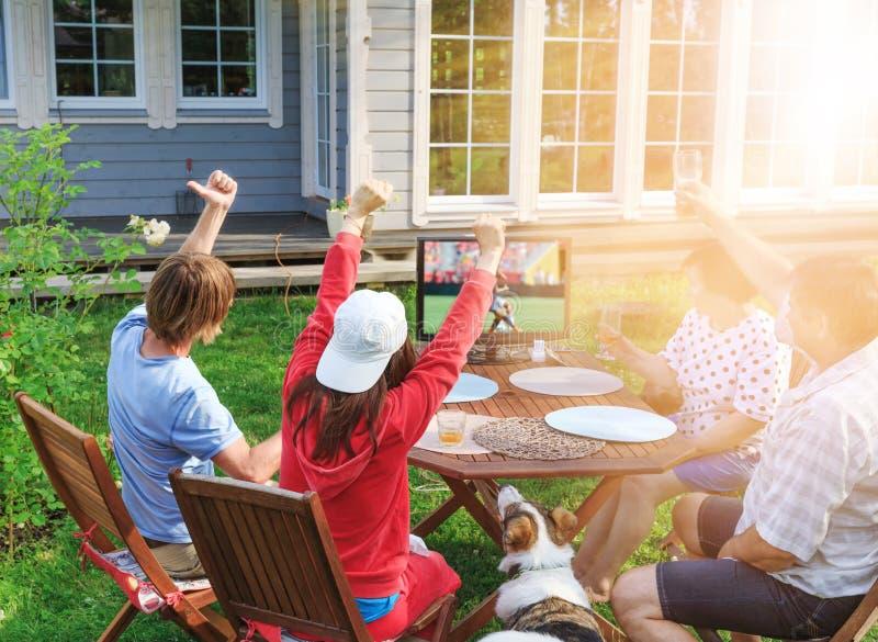 Lycklig familj eller företag av vänner som utomhus håller ögonen på fotboll på TV i borggården av deras hem royaltyfri fotografi