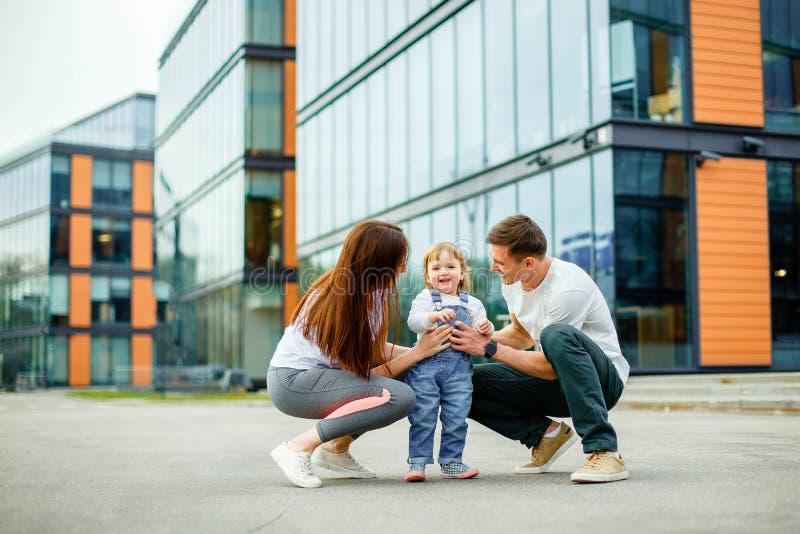 Lycklig familj för stående av tre Barnet uppfostrar att le att spela med deras lilla dotter, medan gå till och med gatorna av royaltyfri bild