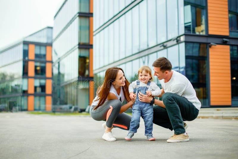 Lycklig familj för stående av tre Unga föräldrar spelar med deras lilla dotter, medan gå till och med gatorna av staden royaltyfri foto