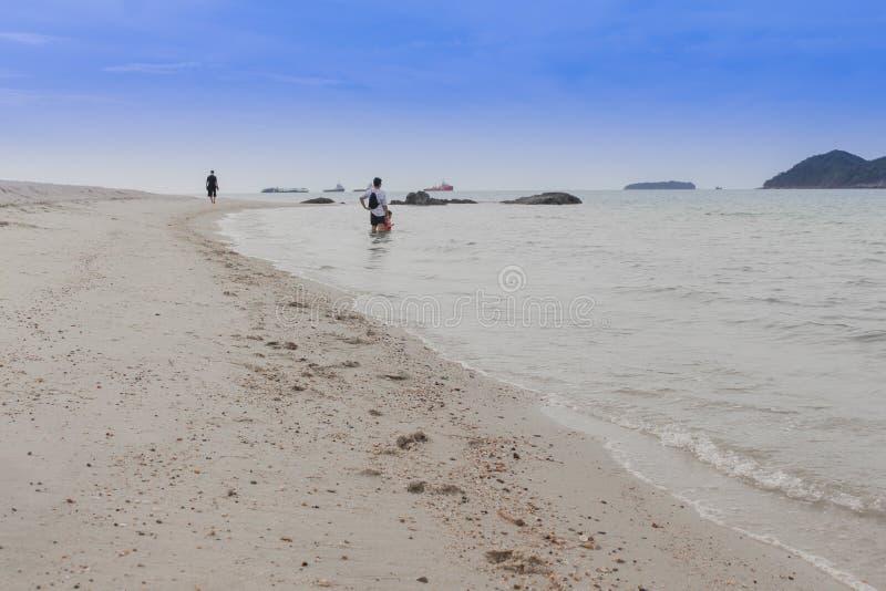 Lycklig familj - faderhållen behandla som ett barn handen går i havet på sommarsemestrar med barn royaltyfri fotografi