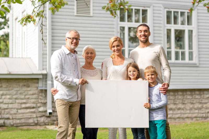 Lycklig familj framme av huset utomhus arkivfoto