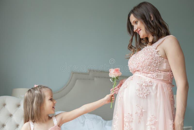 lycklig familj Gravid moder och liten dotter arkivbilder