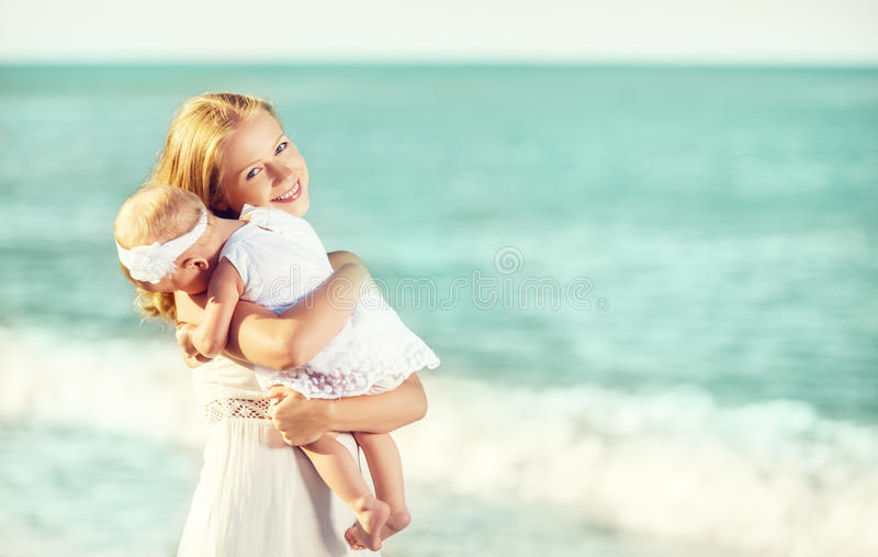 Lycklig familj i den vita klänningen Moderkramar behandla som ett barn i himlen royaltyfria foton