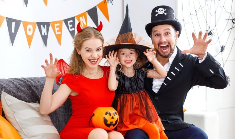 Lycklig familj i dräkter som får klara för halloween royaltyfri bild