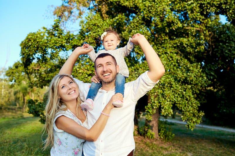 Lycklig familj i en parkera i sommarhöst royaltyfria bilder