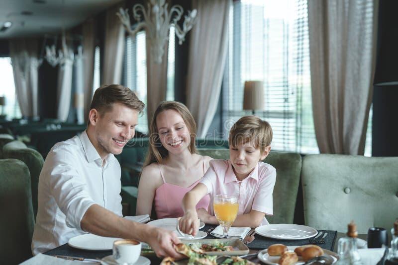 Lycklig familj i en restaurang royaltyfri fotografi