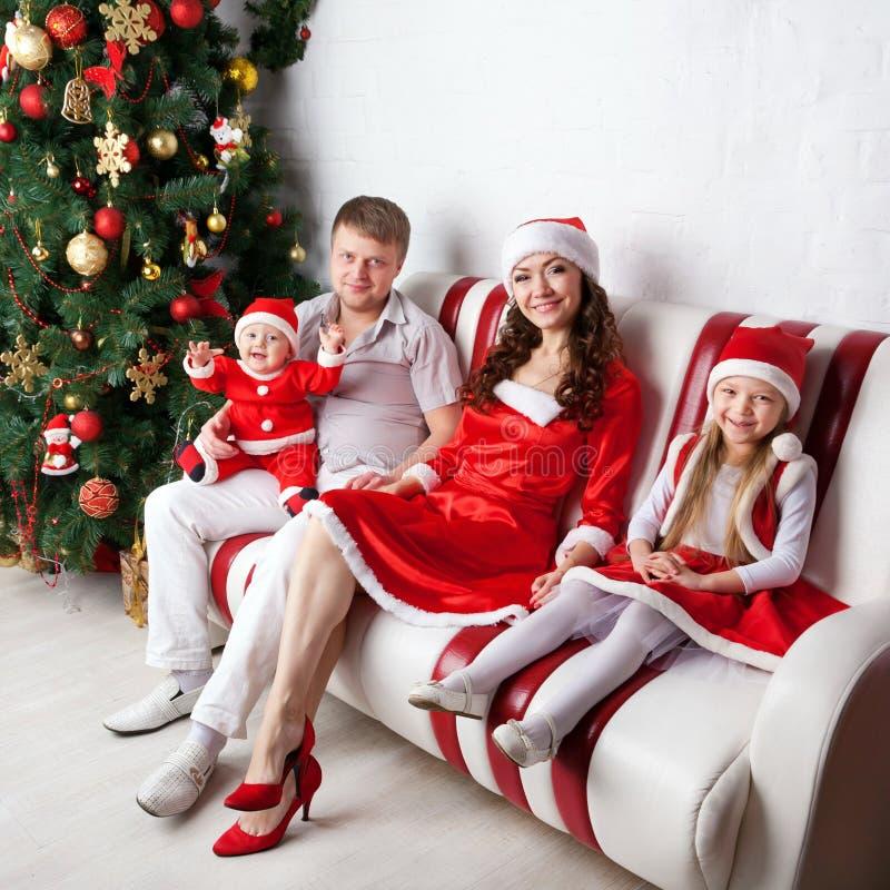 Lycklig familj i jultomtendräkter som firar jul royaltyfria bilder