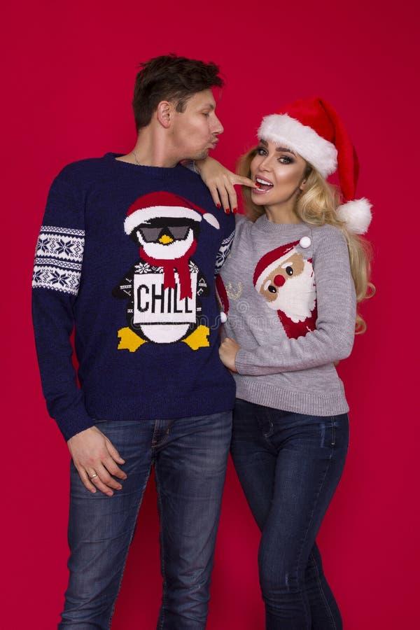 Lycklig familj i jultröjor som poserar på en röd bakgrund i studion Enjoyng förälskelse kramar, semestrar folk togetherness fotografering för bildbyråer