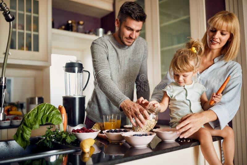 Lycklig familj i kök som gör frukosten royaltyfria bilder