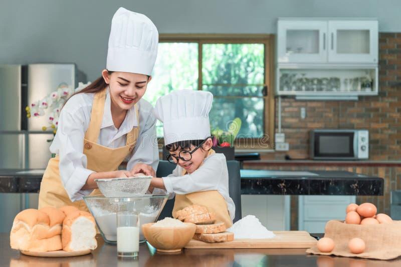 Lycklig familj i k?k moder- och barndottern som f?rbereder degen, bakar kakor arkivbild