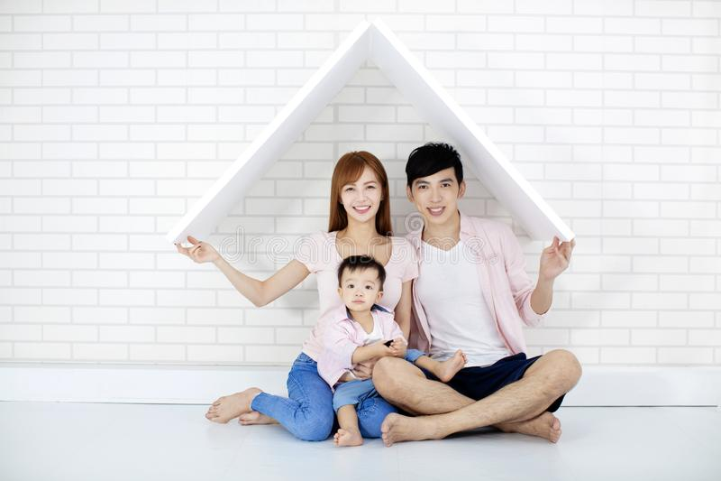 Lycklig familj i nytt hus med taket royaltyfria foton