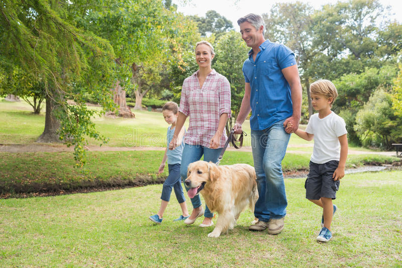 Lycklig familj i parkera med deras hund arkivfoto
