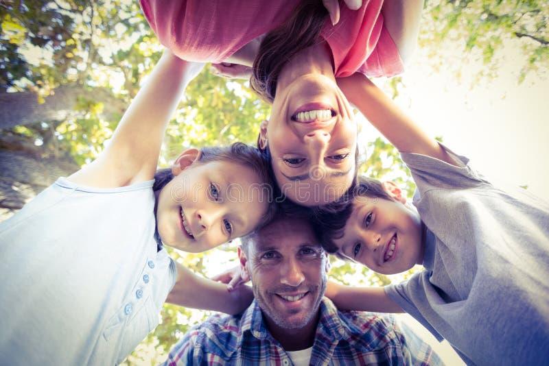 Lycklig familj i parkera som kurar i cirkel arkivbilder