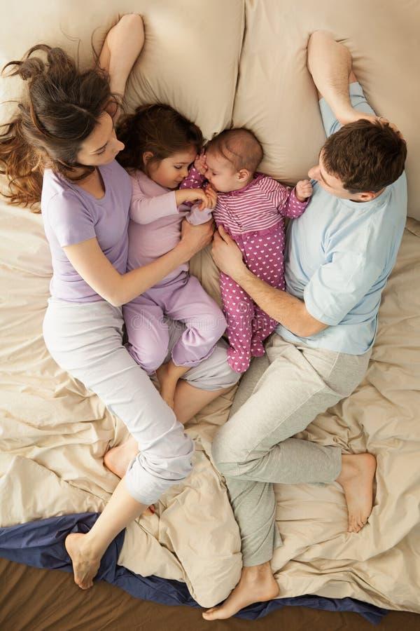 Lycklig familj i säng royaltyfria bilder