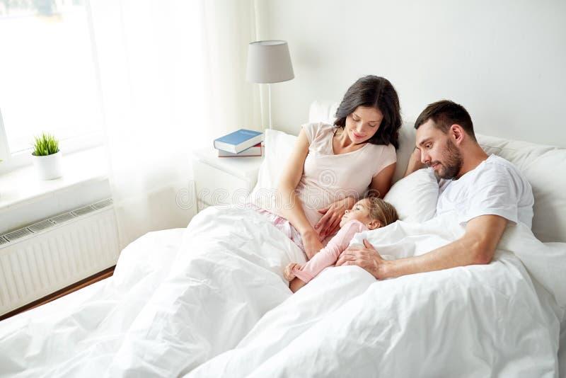 Lycklig familj i säng hemma arkivbild