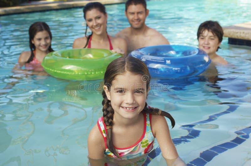 Lycklig familj i simbassäng arkivfoto