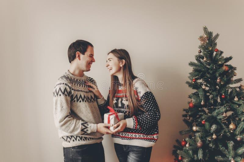 Lycklig familj i stilfulla tröjor som utbyter gåvor i festlig roo royaltyfria foton