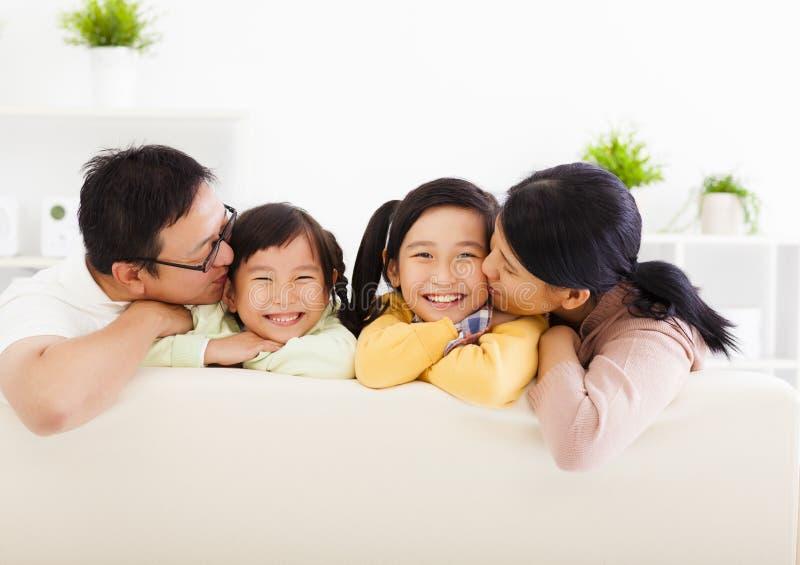 Lycklig familj i vardagsrumet arkivfoton