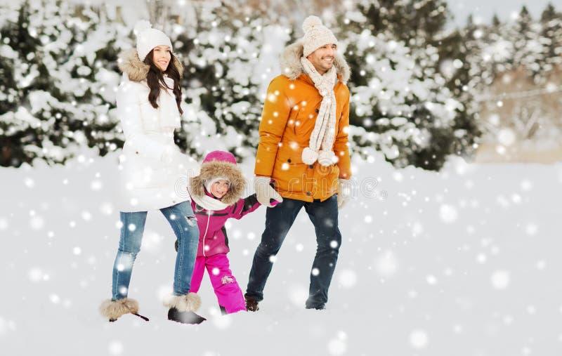 Lycklig familj i vinterkläder som utomhus går royaltyfri fotografi