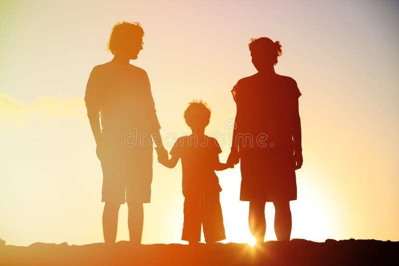 Lycklig familj inklusive gravid moder, fader och son på solnedgången arkivfoton