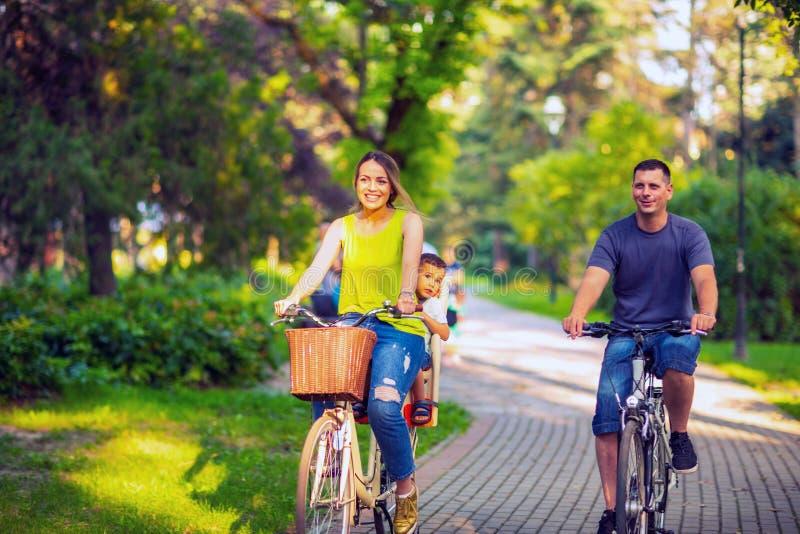 lycklig familj Le fadern och modern med ungen på cykelhav royaltyfri foto