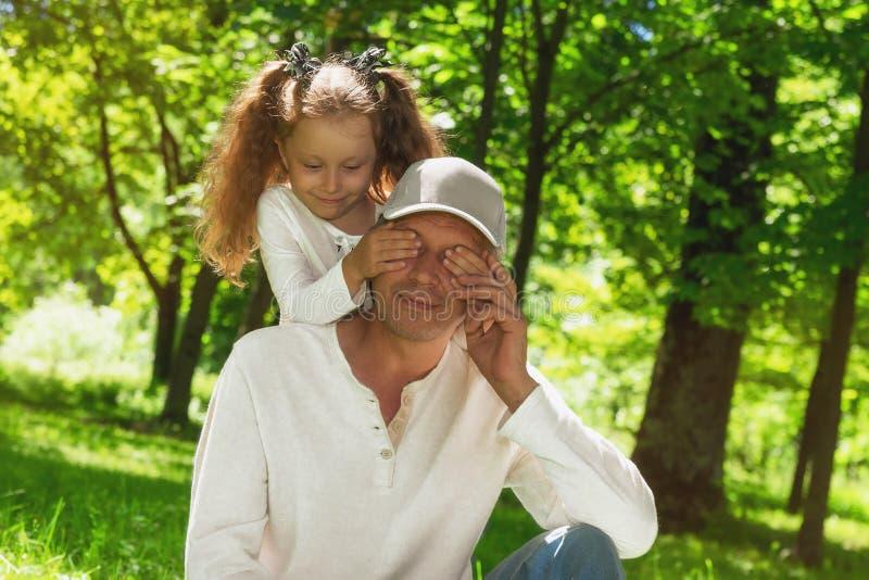 Lycklig familj! Lilla flickan täcker hennes faderögon - hon gör en överraskning royaltyfri bild