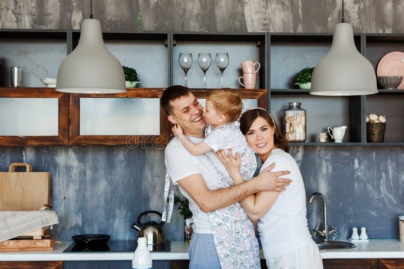 Lycklig familj - mamma, farsa och son i köket hemma i morgonen royaltyfri foto