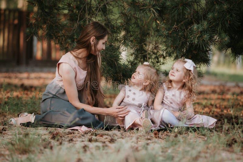Lycklig familj - mamman och tv? d?ttrar sitter i en ?ng och en l?sning en bok picknick arkivfoto