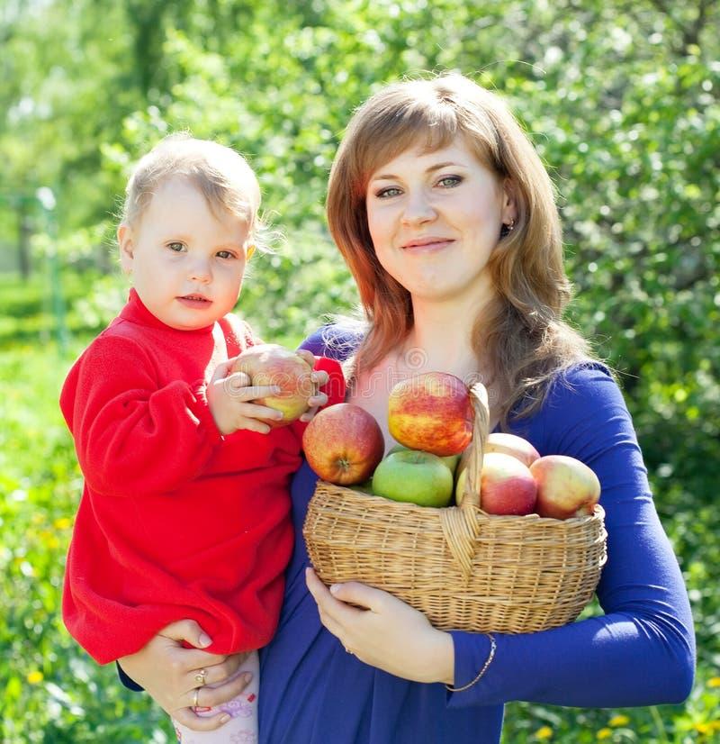Lycklig familj med äpplen i fruktträdgård arkivbild