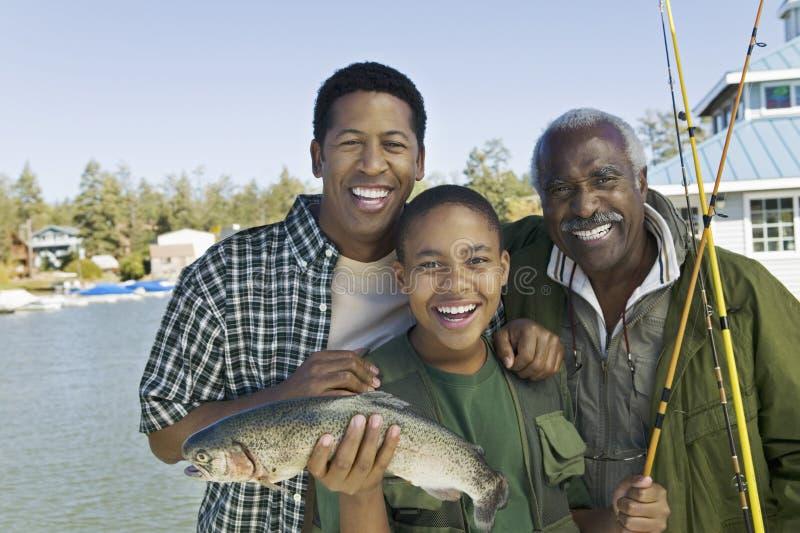 Lycklig familj med att fiska Rod And Fish arkivbild
